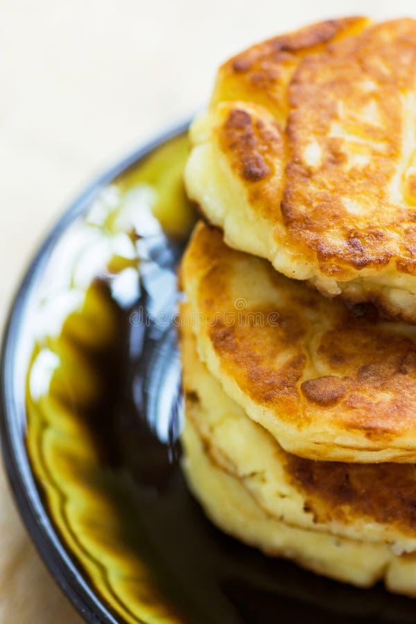 堆积从酸奶干酪的新近地油煎的自创蓬松薄煎饼在木厨房用桌上的黑暗的板材 开胃金黄外壳 库存图片