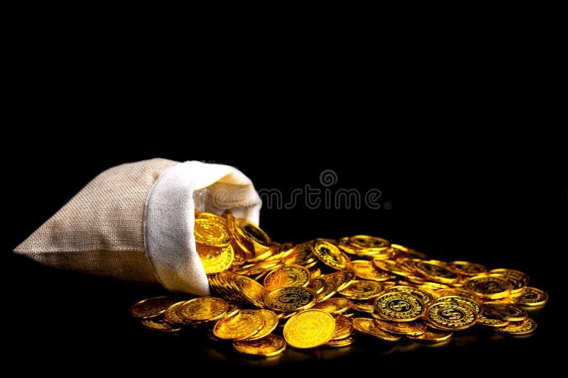 堆积在珍宝大袋的金币在黑背景 免版税库存图片