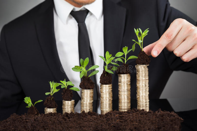 堆积在硬币的商人树苗代表成长 免版税库存图片