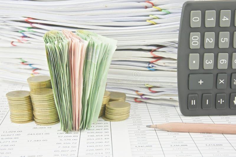 堆积在金币在棕色铅笔附近和计算器之间的票据 免版税库存照片