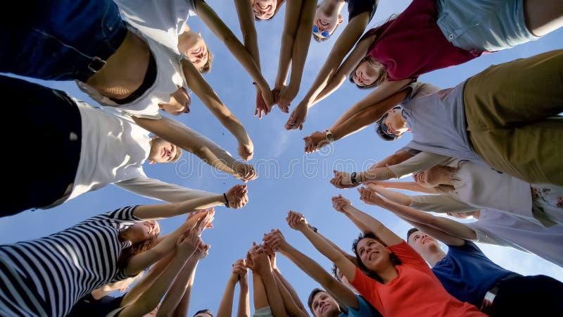 堆积手概念的大学生配合 十九个朋友 免版税库存照片
