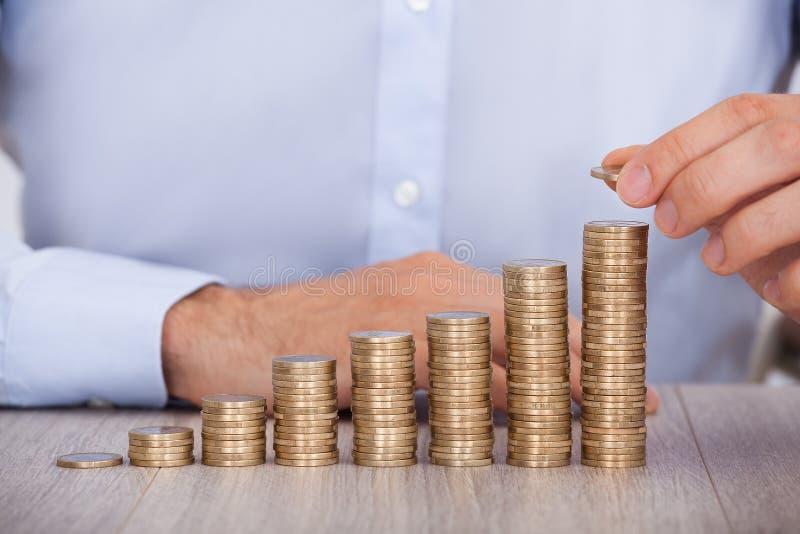 堆积欧洲硬币的商人在书桌 库存图片