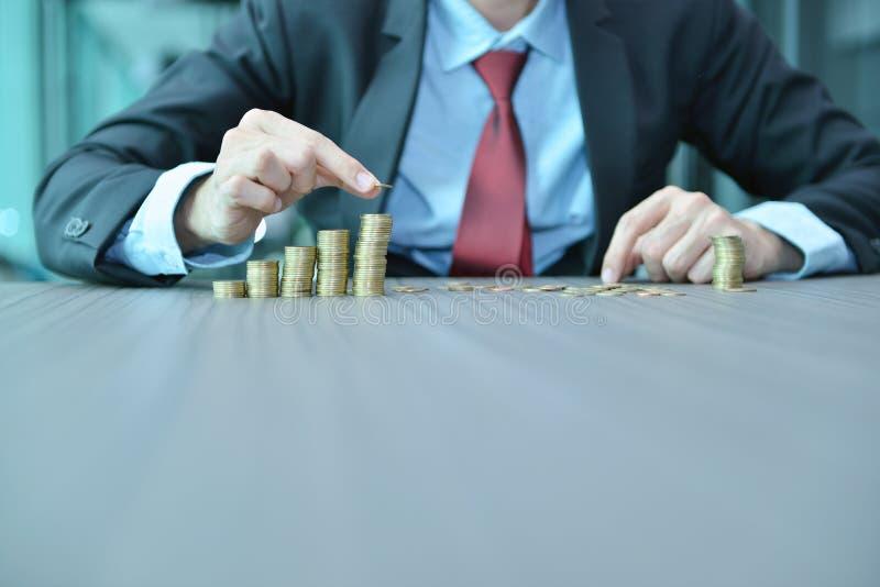堆积硬币按增长的顺序的商人在书桌 图库摄影