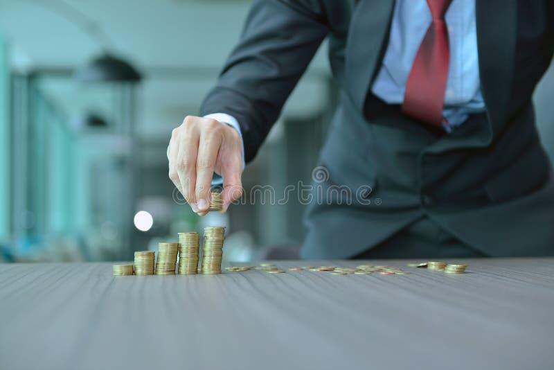 堆积硬币按增长的顺序的商人在书桌 免版税库存图片