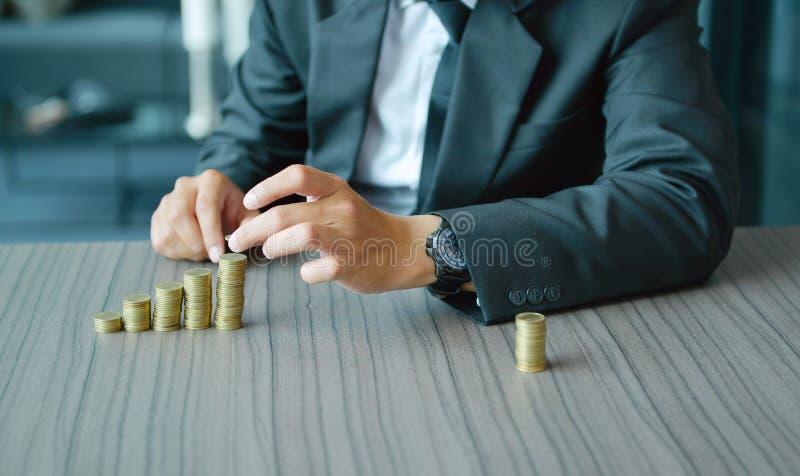 堆积硬币按增长的顺序的商人在书桌 免版税图库摄影