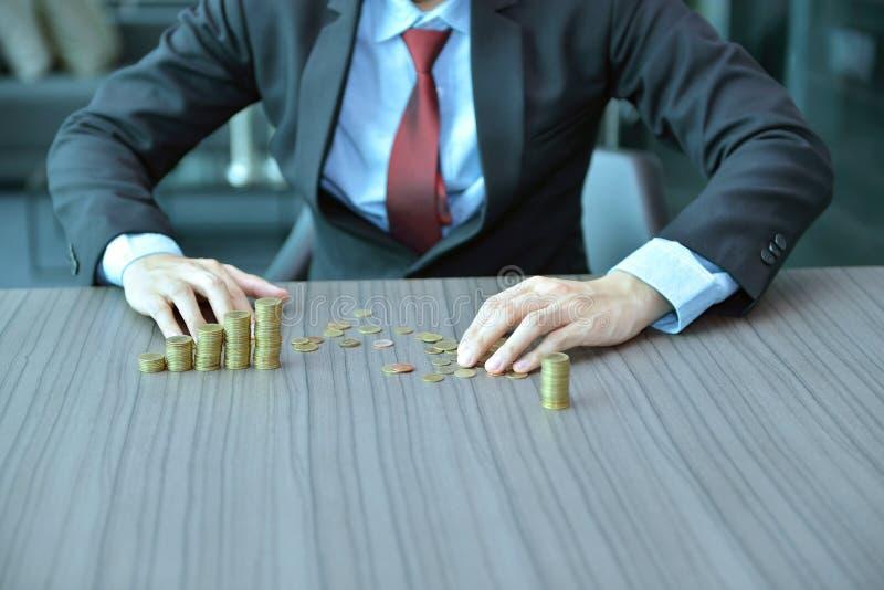 堆积硬币按增长的顺序的商人在书桌 库存照片