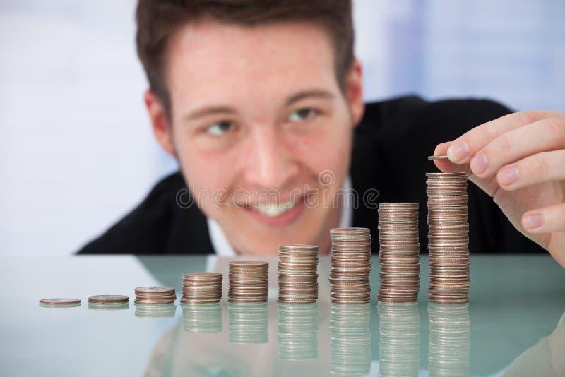 堆积硬币按增长的顺序的愉快的商人 免版税库存照片
