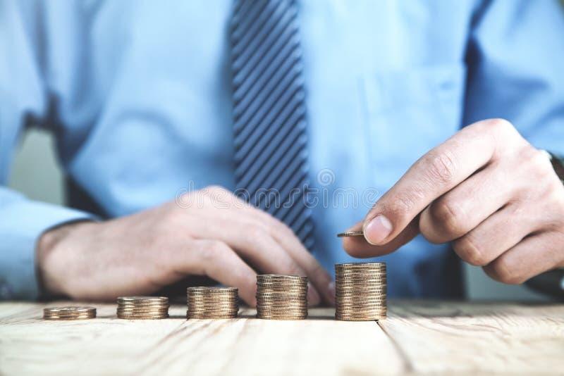 堆积硬币的商人 财务,投资的概念和 库存图片