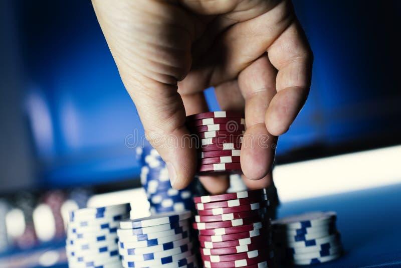 堆积纸牌筹码的幸运球员在赌博娱乐场 图库摄影