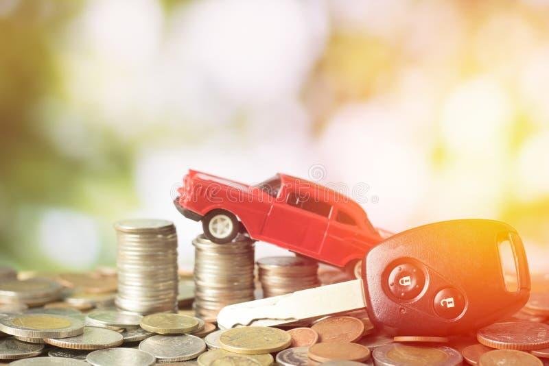 堆积金钱铸造与玩具汽车和钥匙在绿色bokeh backg 免版税库存图片