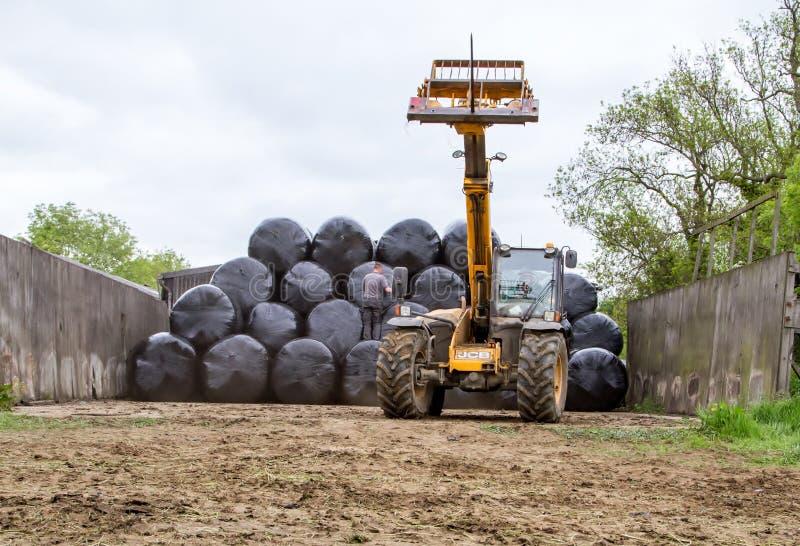 堆积围绕在堆的大包的装载者拖拉机 免版税库存照片