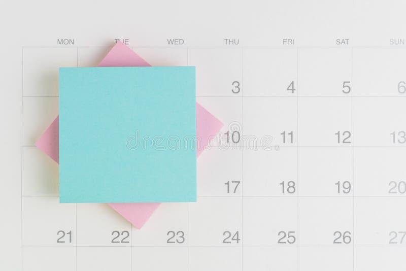 堆稠粘的笔记或黏着性纸与黑空间写的消息在白色干净的日历使用作为提示在假期 库存图片