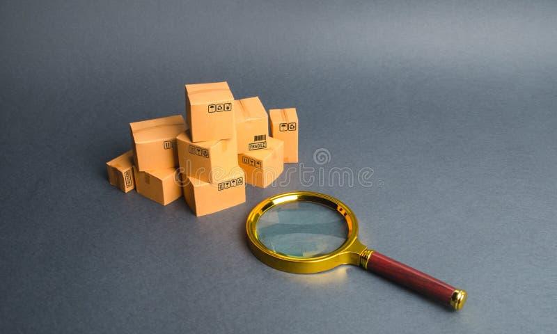 堆箱子和放大镜 概念查寻商品和服务 跟踪小包通过互联网 质量管理 免版税图库摄影