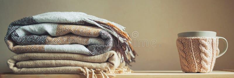 堆米黄方格的羊毛毯子和杯子在一个木胸口秋天概念 免版税图库摄影