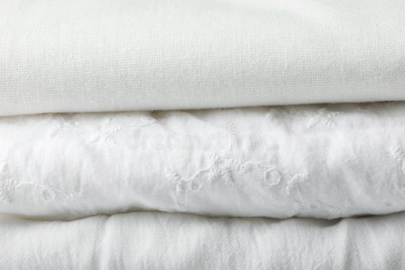 堆纯净的有机棉花和亚麻制被折叠的织品飞机和与小孔鞋带样式 衣物洗衣店家纺织品概念 库存照片