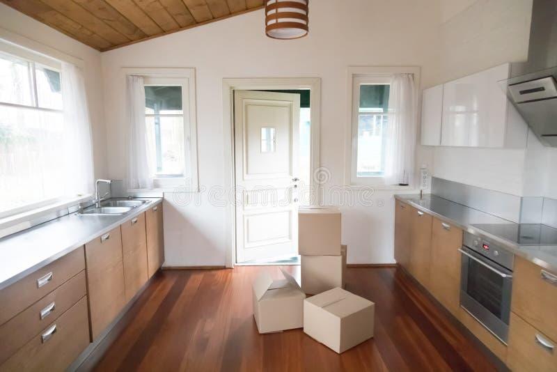 堆纸板箱在新的现代厨房里 免版税库存图片