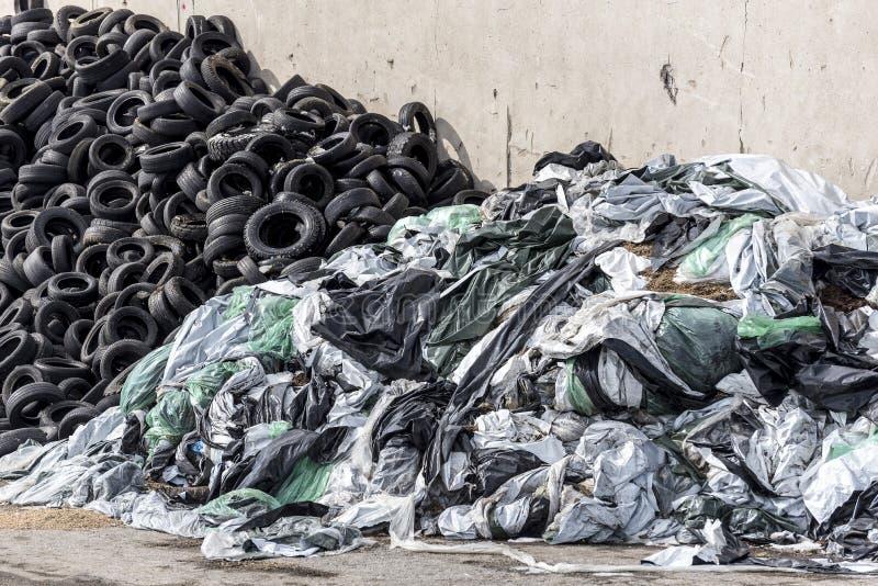 堆老使用的轮胎和第二在老墙壁上的堆塑料袋和塑料 库存图片