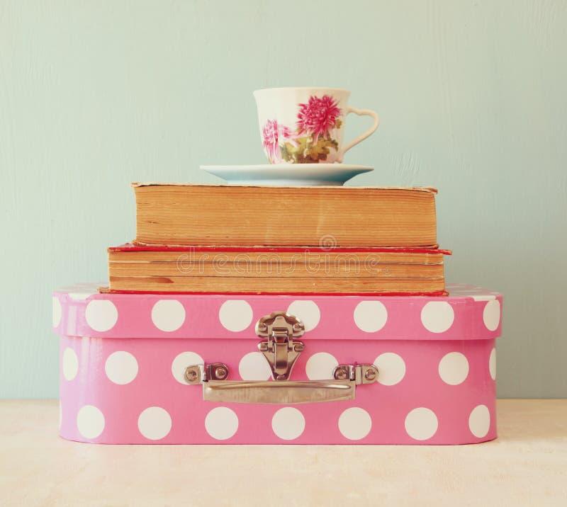 堆老手提箱、书和葡萄酒茶杯在木桌 棒图象夫人减速火箭的抽烟的样式 免版税图库摄影