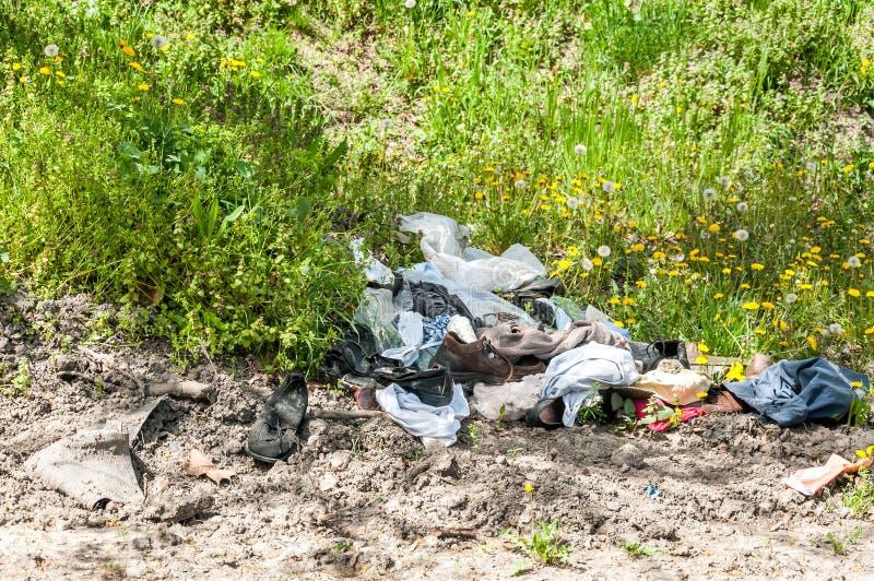 堆老衣裳和鞋子在草倾销了作为破烂物 库存图片
