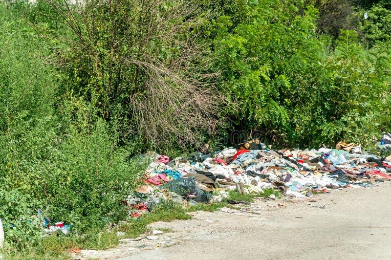 堆老衣裳和鞋子在草倾销了作为,乱丢和污染环境的破烂物和垃圾 免版税库存图片