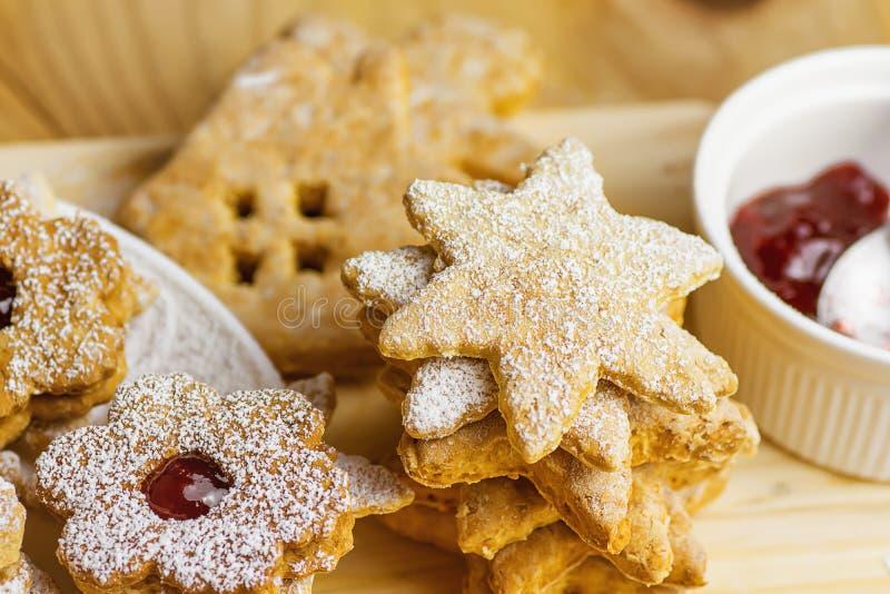 堆自创姜饼和脆饼Linzer曲奇饼各种各样的形状星议院花用搽粉的果酱 木表 库存照片