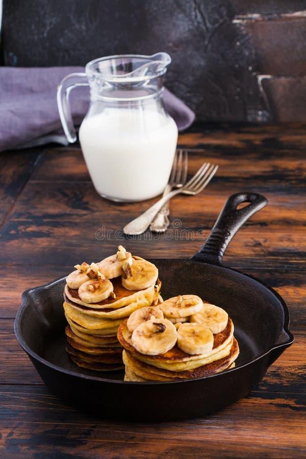 堆自创薄煎饼用香蕉、枫蜜和核桃在黑生铁长柄浅锅 免版税库存照片