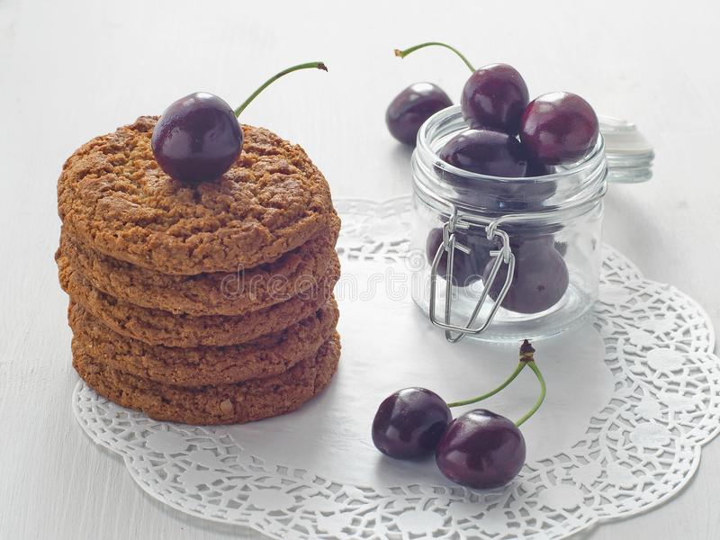 堆自创麦甜饼装饰用与瓶子的成熟樱桃有很多在白色木桌上的新鲜的樱桃 免版税库存照片