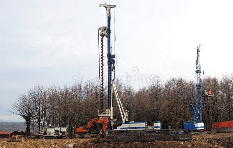 堆船具、一台移动式起重机和挖掘机的被跟踪的木钻在新的工地工作开头  库存图片