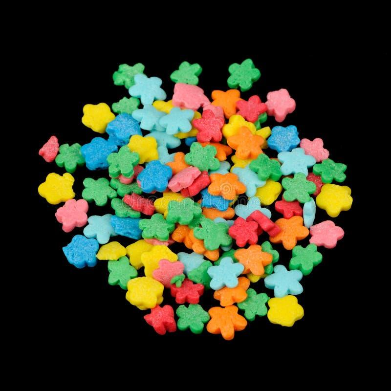 花型五颜六色的糖在黑背景洒(可食的蛋糕装饰) 免版税库存图片