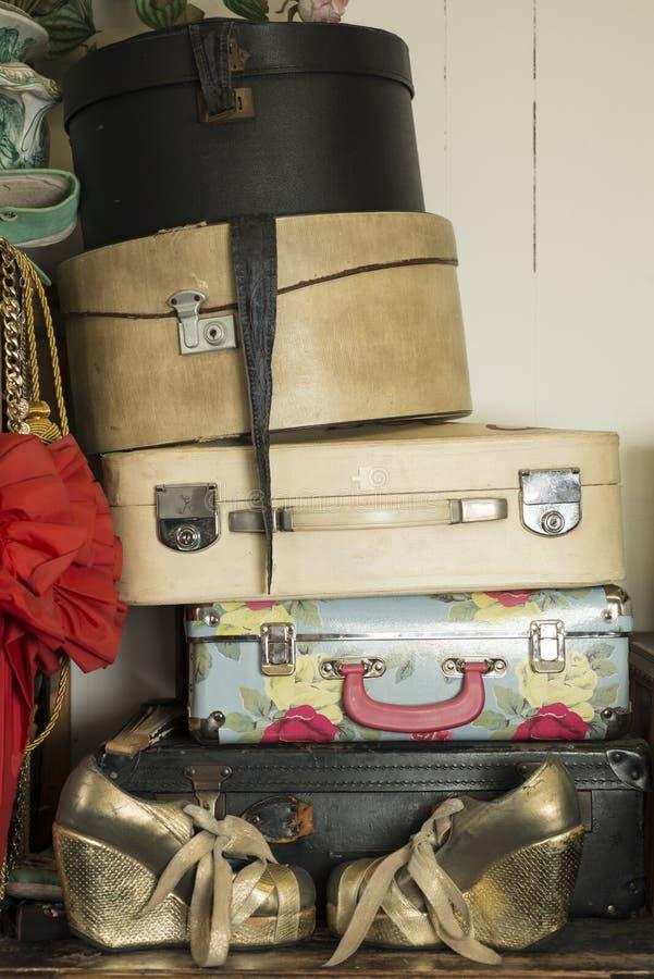 堆葡萄酒手提箱和一个对金黄鞋子 图库摄影