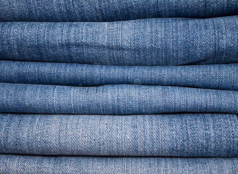 堆蓝色牛仔裤各种各样的树荫作为背景的 免版税库存照片