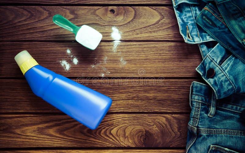 堆蓝色牛仔裤穿衣与洗涤剂和洗衣粉, 库存照片