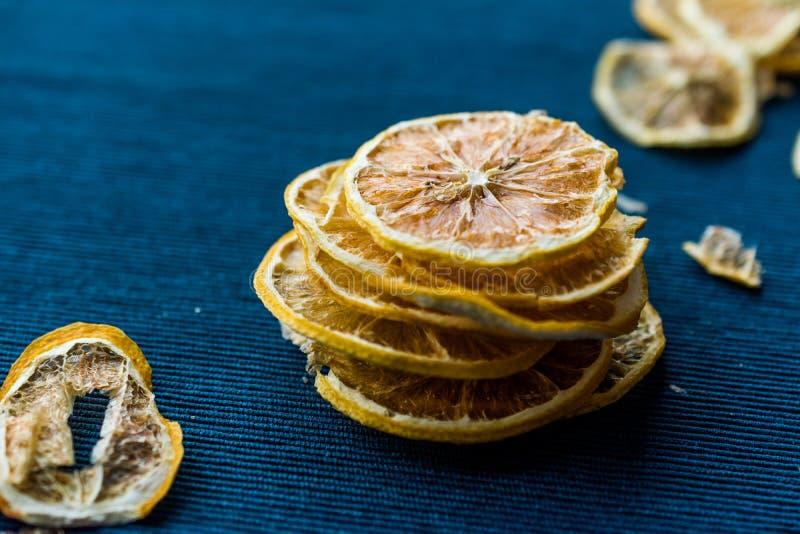 堆蓝色表面上的干柠檬切片/干燥和切 免版税图库摄影