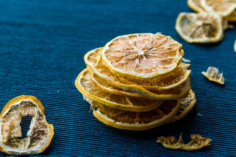 堆蓝色表面上的干柠檬切片/干燥和切 免版税库存图片