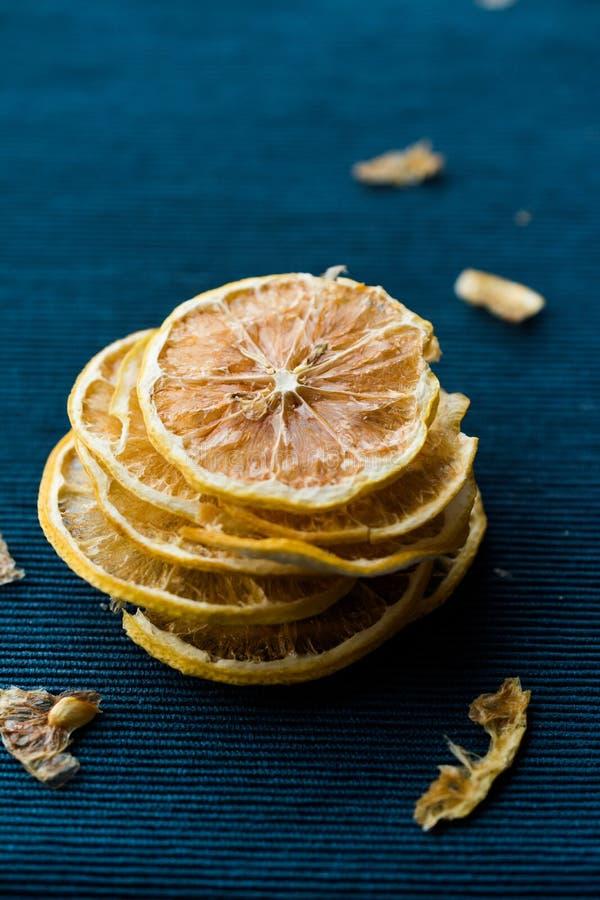 堆蓝色表面上的干柠檬切片/干燥和切 免版税库存照片