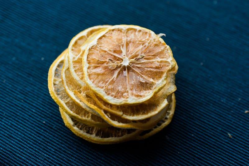 堆蓝色表面上的干柠檬切片/干燥和切 库存照片