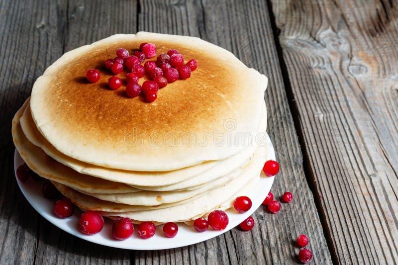 堆薄煎饼用在一块白色板材的蔓越桔在木板背景 图库摄影