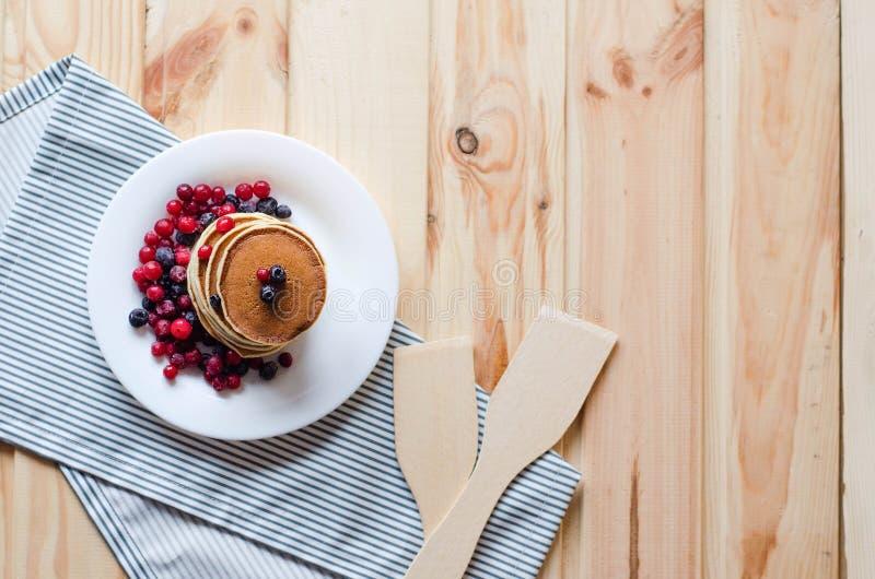 堆薄煎饼用蓝莓和蔓越桔在一块白色板材 库存照片