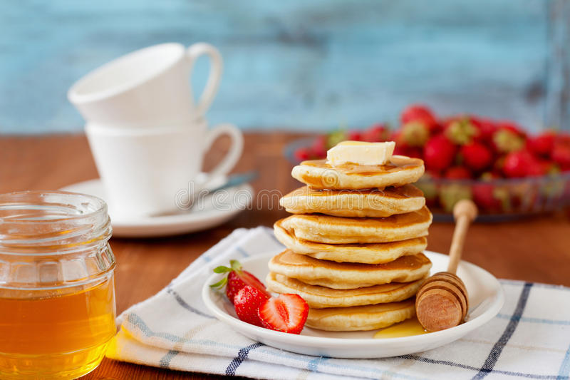 堆薄煎饼用蜂蜜糖浆、黄油和草莓在一块白色板材 库存图片
