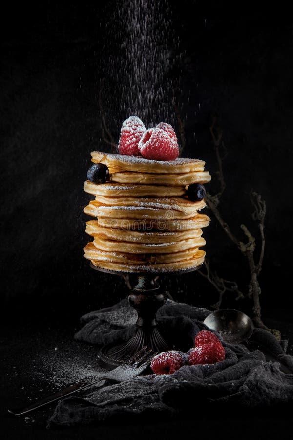 堆薄煎饼装饰用莓果和搽粉的糖,土气演播室射击 免版税库存照片
