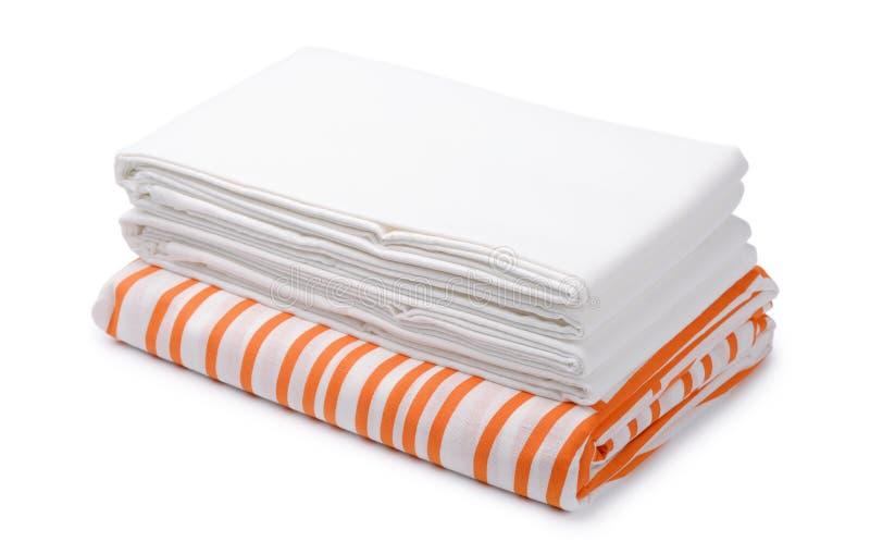 堆被折叠的白色和颜色卧具覆盖 免版税库存照片