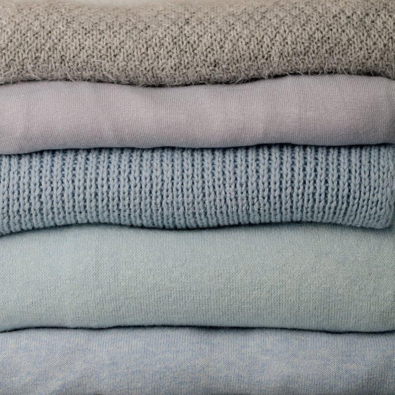 堆被编织的衣裳毛线衣,围巾,套头衫蓝色, whi 库存图片