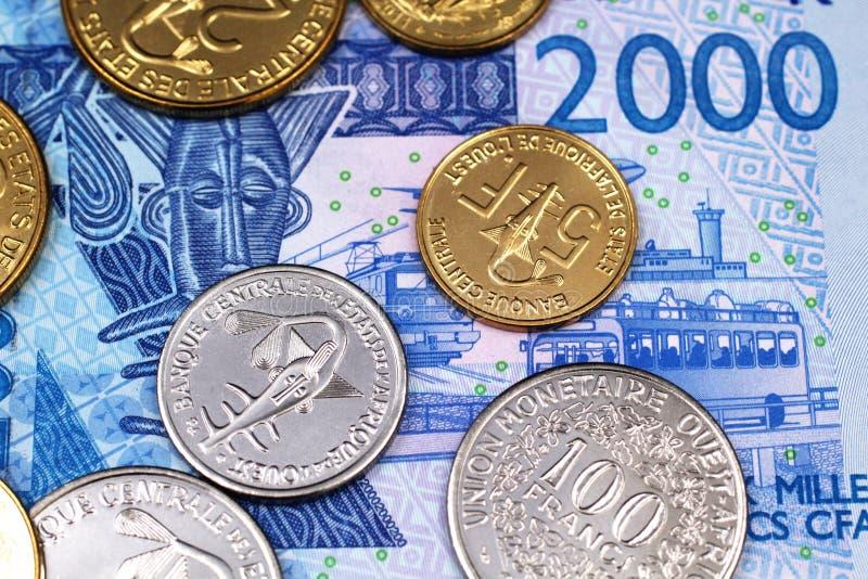 堆西非法郎硬币在2000西非法郎笔记关闭  免版税库存照片