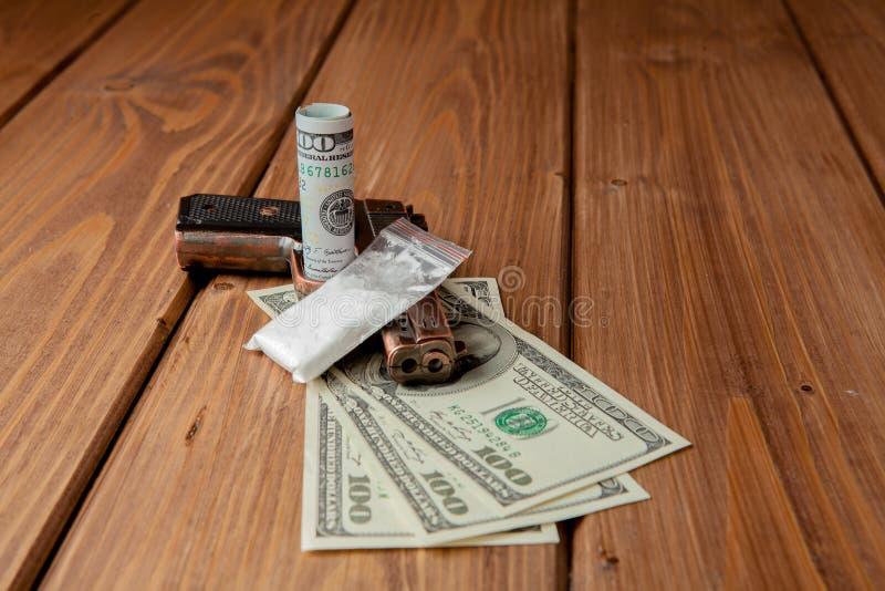 堆金钱、关于危险的drugsand在一张木桌上的一杆枪,药物的概念和威胁 免版税库存照片