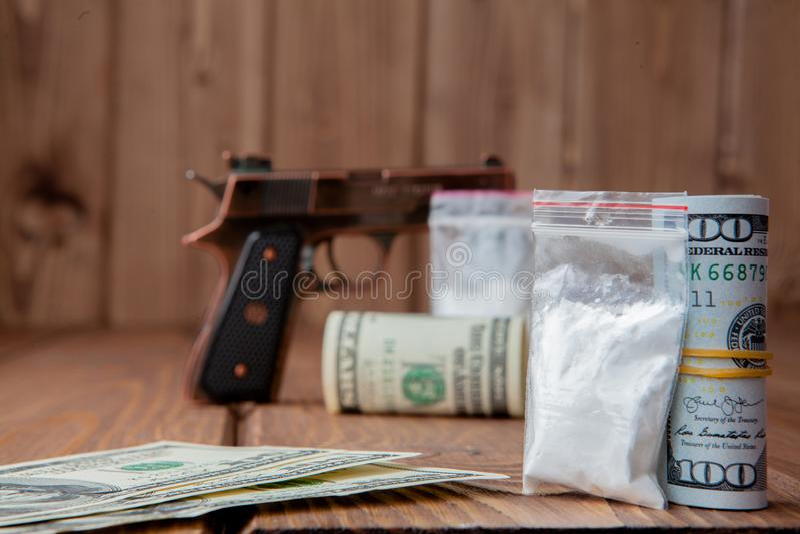 堆金钱、关于危险的drugsand在一张木桌上的一杆枪,药物的概念和威胁 免版税库存图片
