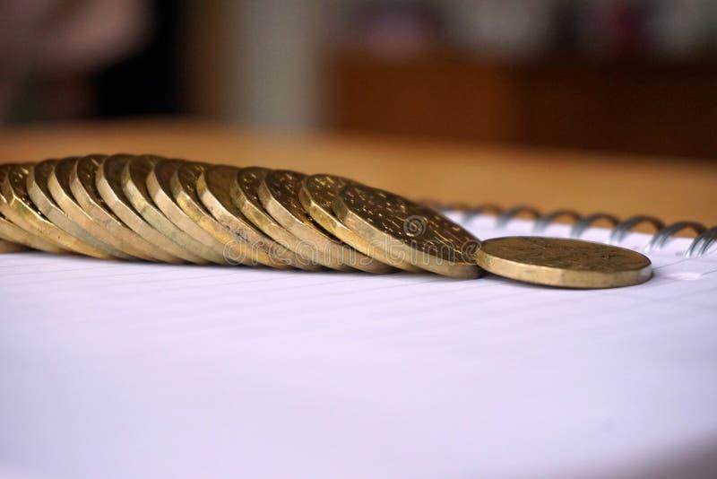 堆金钱背景币金和镀金面金属在纸笔记薄 库存照片