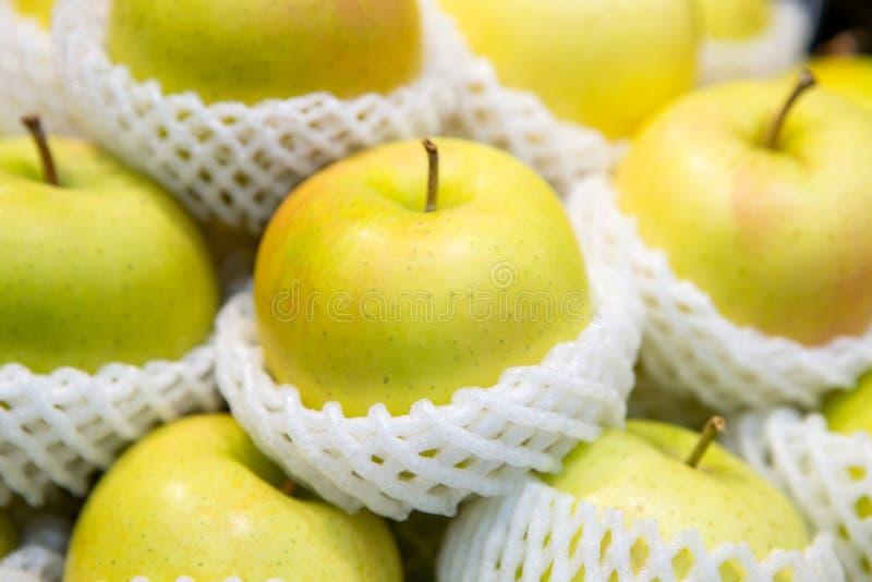 堆金黄苹果计算机包裹与泡沫网在新鲜市场上 库存照片