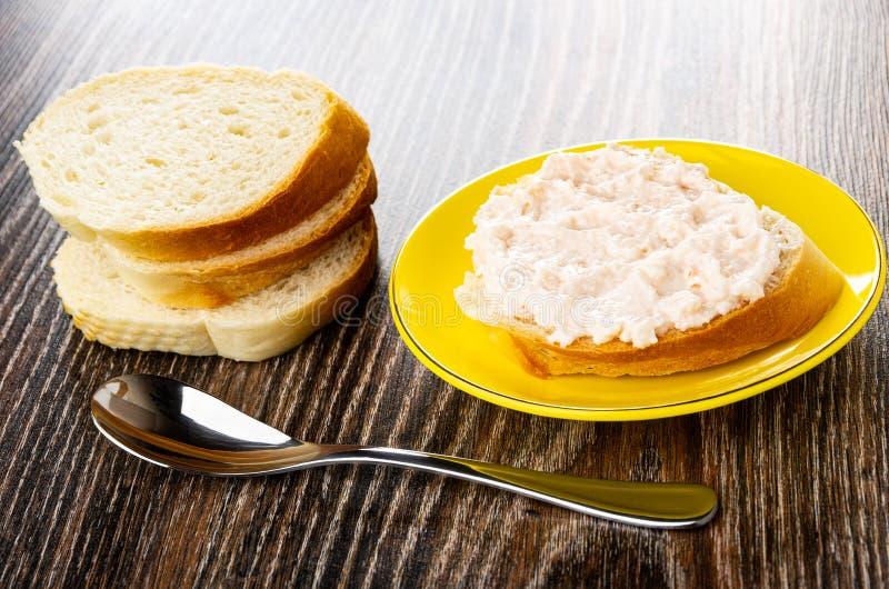 堆面包,与磷虾浆糊的三明治在茶碟,在木桌上的匙子 免版税库存照片