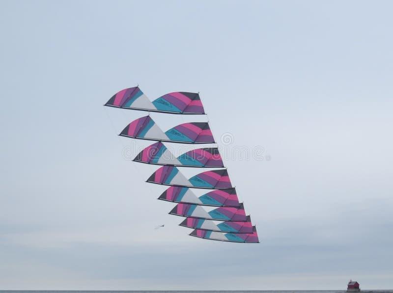 堆革命特技风筝飞行在密执安湖 库存图片