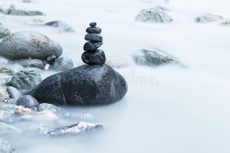 堆黑石头在河 免版税库存照片